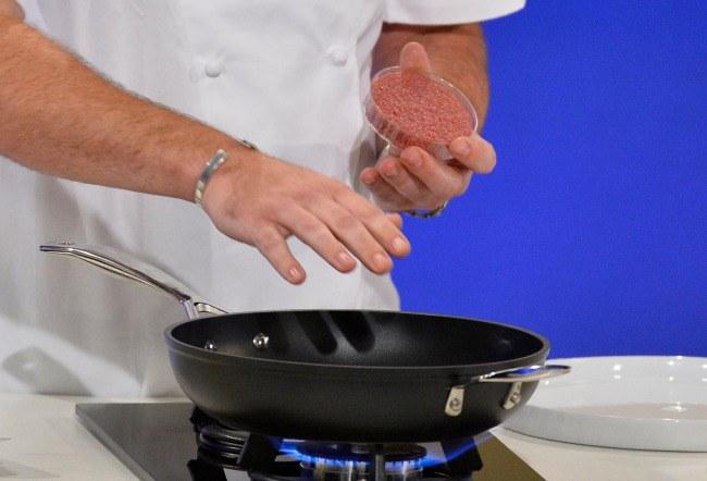 Virtuvės šefas Richas McGeownas rengiasi kepti pirmąjį pasaulyje laboratorijoje išaugintos jautienos mėsainį per pristatymo renginį vakarų Londone 2013 rugpjūčio 5 d.