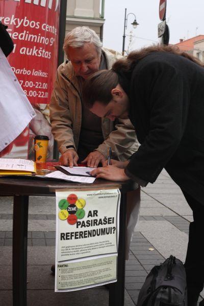 Dėl referendumo pasirašo Romualdas, šalia jo stovi R. Radzevičius. Ekspertai.eu nuotr.